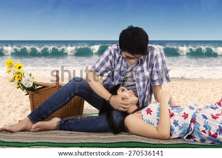 Portrait of young asian couple enjoy holiday at the beach, sitting on mat while looking at each other with lovely - stock photo