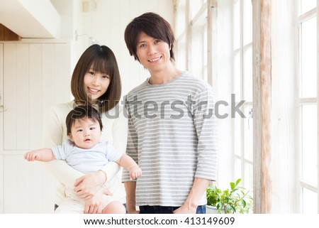 portrait of young asian family relaxing in room