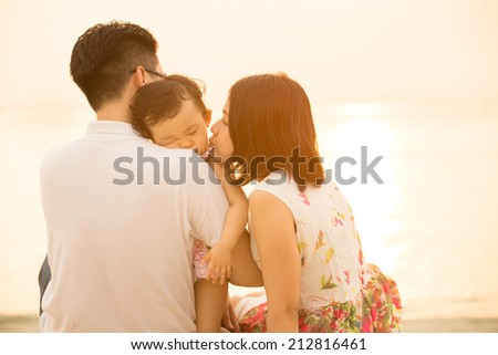 Portrait of young Asian family seated on beach outdoor vacation, during summer sunset, natural sunlight with flare. - stock photo