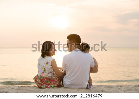 Portrait of young Asian family seated on beach outdoor vacation, during summer sunset, natural sunlight.  - stock photo