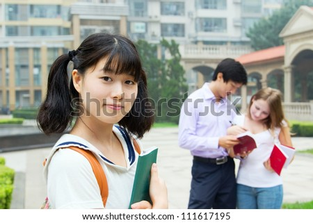 Portrait of young asian girl holding book. Beautiful female student with book. Students study outside college - stock photo