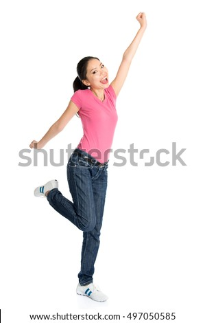 Portrait of young Asian girl in pink shirt and jeans jumping happily, full body standing isolated on white background.