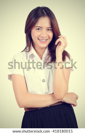 Portrait of Young Asian girl in Thai university student uniform (vintage color toned image) - stock photo