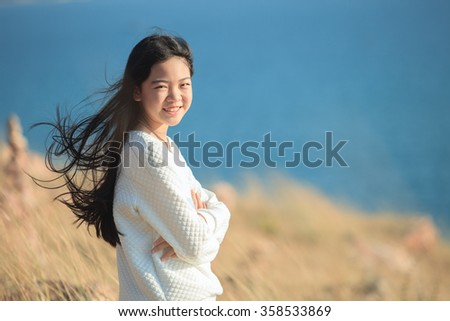 portrait of young asian girl  smiling face happiness emotion with blue blur background  - stock photo