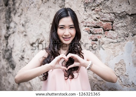 Portrait of young asian girl with grunge wall background - stock photo
