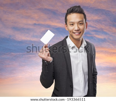 portrait of young asian man showing a visit card