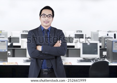 Portrait of young asian manager with confident expression, standing in the office - stock photo
