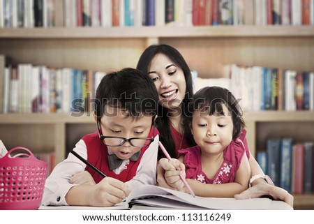 Portrait of young asian mother guiding her children to draw on the paper. shot in the library - stock photo