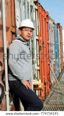 Portrait of Young Asian specialist, engineer with white safety helmet, hard hat and safety glass.