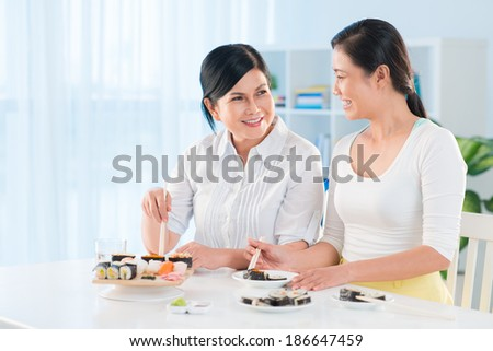 Portrait of young Asian woman and her mother eating sushi in the kitchen - stock photo