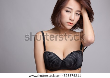 Portrait of young asian woman in sexy black bra or lingerie with big boobs, headache or boring concept. - stock photo