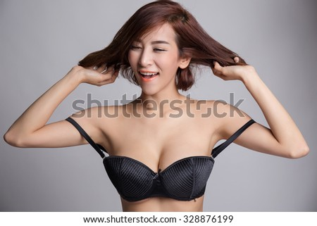 Portrait of young asian woman in sexy black bra or lingerie with big boobs playing with her hair. - stock photo