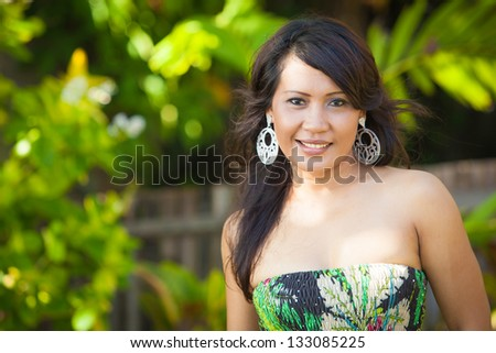 Portrait of young asian woman with floral dress in Bali - stock photo