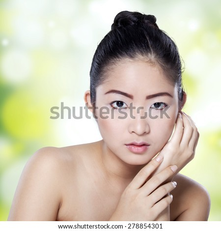 Portrait of young asian woman with lovely face and beauty perfect skin looking at the camera against defocused light background