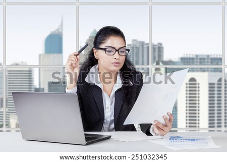 Portrait of young asian woman working in the office while reading a paperwork - stock photo