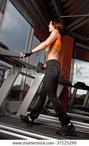 Portrait of young athlete doing exercise on treadmill