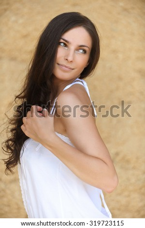 Portrait of young attarctive brunette serious woman wearing white clothes against beige background.