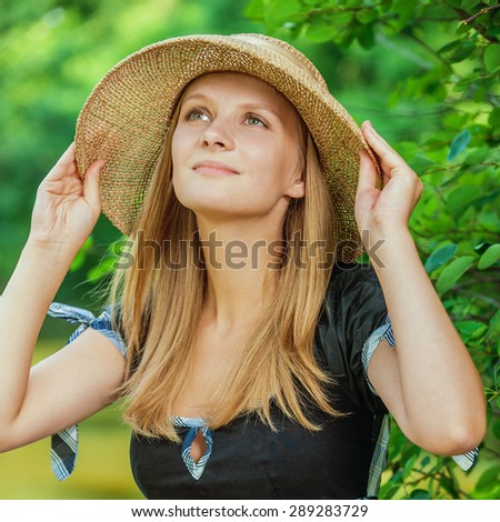 Portrait of young attarctive woman wearing straw hat at summer green park. - stock photo