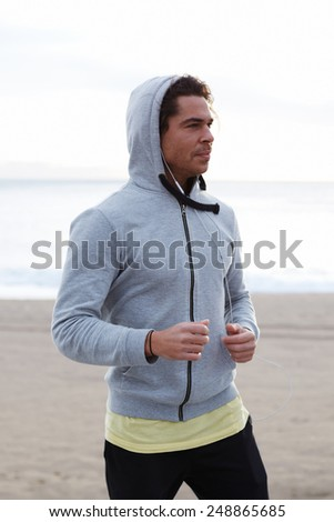 Portrait of young attractive athlete taking break after fitness training outdoors, male runner standing on the beach looking away - stock photo