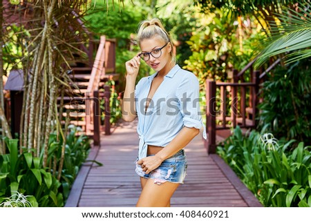 Portrait of young attractive blonde woman wearing eyeglasses - stock photo