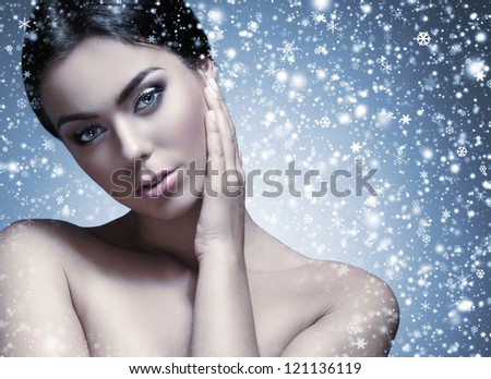 Portrait of young attractive brunette over winter background - stock photo