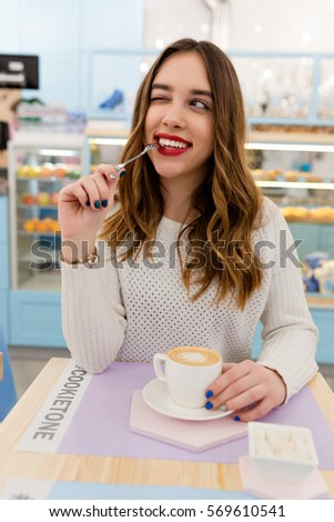 Portrait of young attractive brunette with playful smile and red lipstick. She is sitting in cafe in white pullover and drinks coffee.