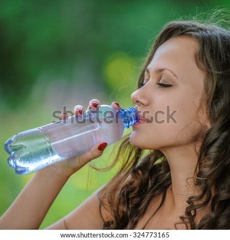 Portrait of young attractive brunette woman drinking water at summer green park.