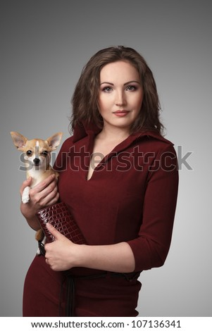 Portrait of young attractive brunette woman holding little Chihuahua dog on her hands - stock photo
