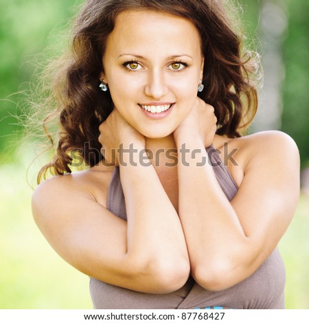 Portrait of young attractive brunette woman wearing blue-brown top at summer green park. - stock photo