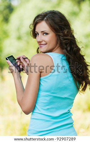 Portrait of young attractive brunette woman wearing blue t-shirt, working with smartphone and stylus at summer green park.