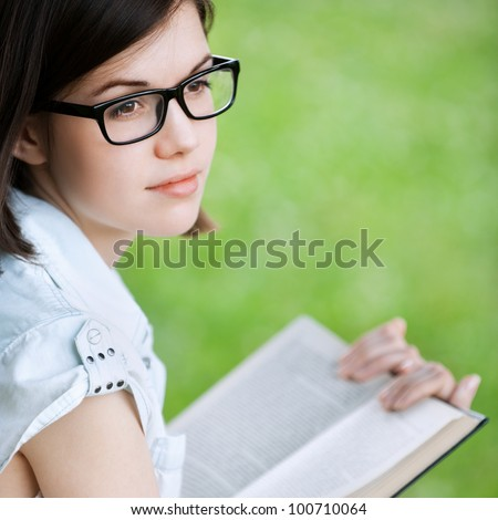 Portrait of young attractive brunette woman wearing glasses, reading book, sitting at summer green park
