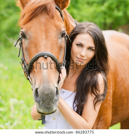 Portrait of young attractive brunette woman wearing white dress with horse at summer green park. - stock photo