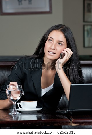 Portrait of young attractive business woman drinking coffee and talking on a cell phone - stock photo