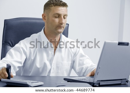 Portrait of young attractive businessman in office environment
