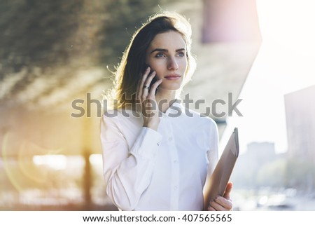 Portrait of young attractive businesswoman talking on her smartphone, close-up of smiling businesswoman in white shirt talking on mobile phone outdoors near her office, flare light - stock photo