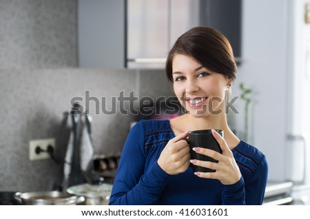 Portrait of young attractive caucasian brunette housewife at kitchen. Morning with cup of coffee. - stock photo