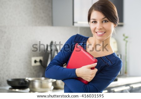 Portrait of young attractive caucasian brunette housewife at kitchen with tablet pc.