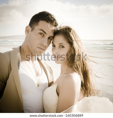 Portrait of young attractive caucasian couple on beach at sunrise - stock photo