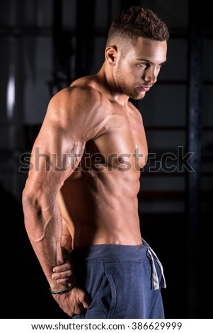 Portrait of young attractive caucasian muscular man working out in gym, showing triceps, abs muscles - stock photo