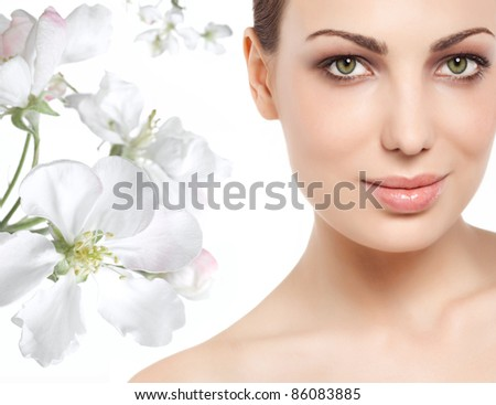 portrait of young attractive caucasian woman  looking at camera with spring flowers - stock photo