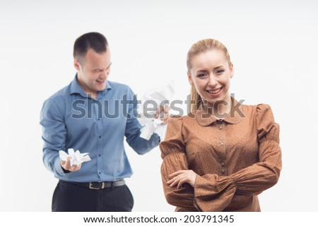 Portrait of young attractive cheerful employee smiling while her colleague on the background crumpling paper in anger, isolated on white - stock photo