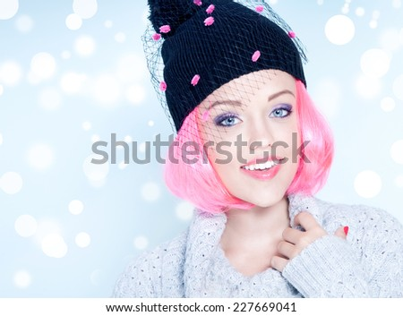 Portrait of young attractive cheerful woman with pink hair wearing fancy winter hat. Christmas concept. - stock photo