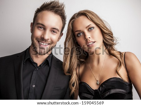 Portrait of young attractive couple posing at studio dressed in black fashionable clothes.  - stock photo