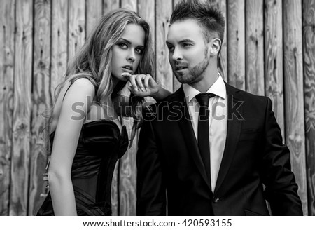 Portrait of young attractive couple posing outdoor against wooden background in black fashionable clothes. Black-white fashion photo.