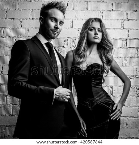 Portrait of young attractive couple posing studio dressed in black fashionable clothes black white
