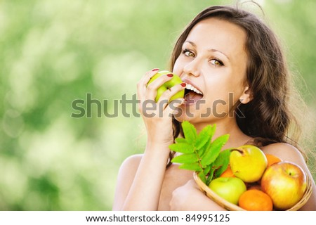 Portrait of young attractive dark-haired smiling woman holding basket full of fruits and eating apple at summer green park.