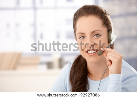 Portrait of young, attractive dispather talking on headphones, smiling.? - stock photo