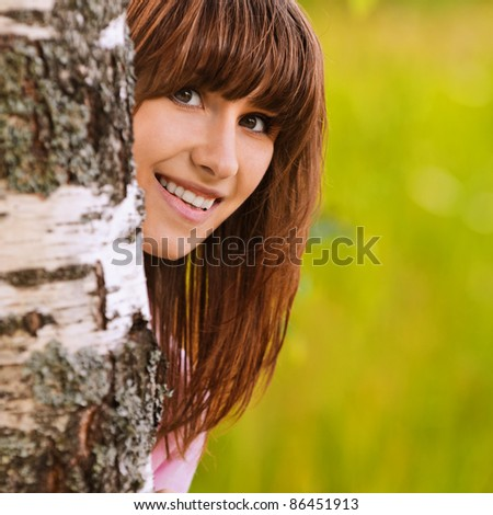 Portrait of young attractive funny smiling dark-haired girl looking from behind birch tree at summer green park. - stock photo