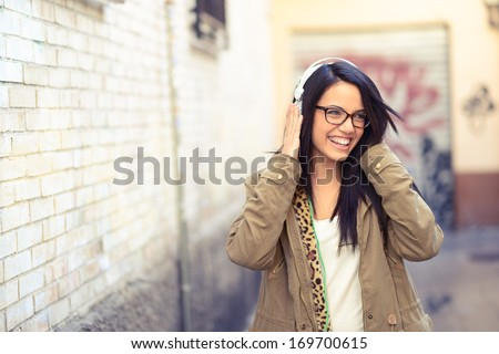 Portrait of young attractive girl in urban background listening to music with headphones - stock photo