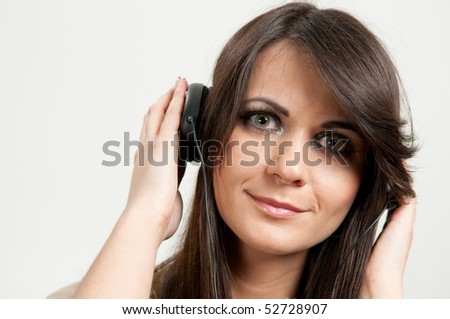 Portrait of young attractive girl listening to music - stock photo